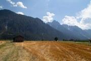 veld met schuur en bergen op de achtergrond