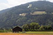 Veld met schuur en 2 paragliders die landen
